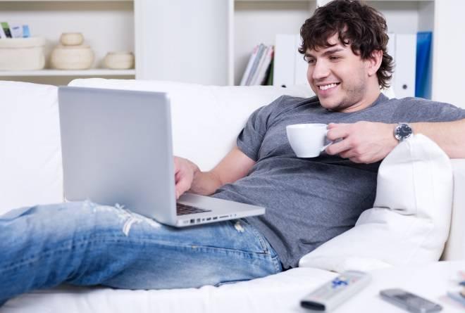Парень улыбается читая ноутбук